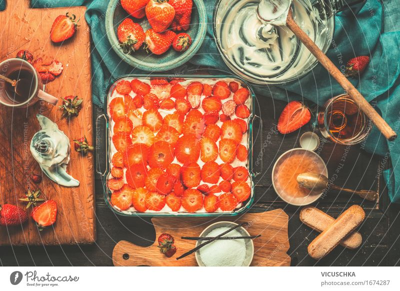Tiramisu mit Erdbeeren. Zubereitung auf dem Küchentisch dunkel Leben Foodfotografie Stil Lebensmittel Design Frucht Häusliches Leben Ernährung Glas Tisch