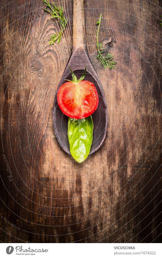 Hälfte von Tomate und Basilikumblatt in Kochlöffel Natur Gesunde Ernährung Leben Essen Foodfotografie Stil Holz Lebensmittel Design Tisch
