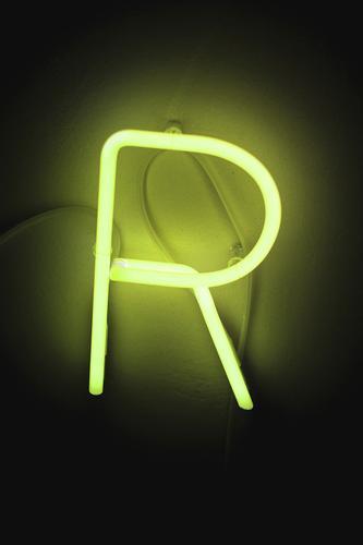 R Zeichen Schriftzeichen dunkel gelb grün Leuchtreklame Leuchtstoffröhre Licht Beleuchtung Beleuchtungselement Farbfoto Innenaufnahme Menschenleer