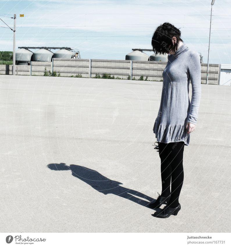 Den Kopf hängen lassen Frau Junge Frau Schatten Kontrast Sonnenlicht grau Kleid Minikleid Traurigkeit Frustration Einsamkeit Beton Platz bleich Gedeckte Farben