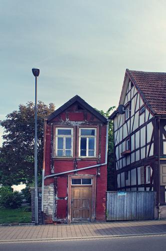 luxusvilla | AST9 alt rot Haus Gebäude Neigung Straßenbeleuchtung Dorf Verfall Altstadt Unbewohnt skurril Kleinstadt Einfamilienhaus schmal Hessen Fachwerkhaus