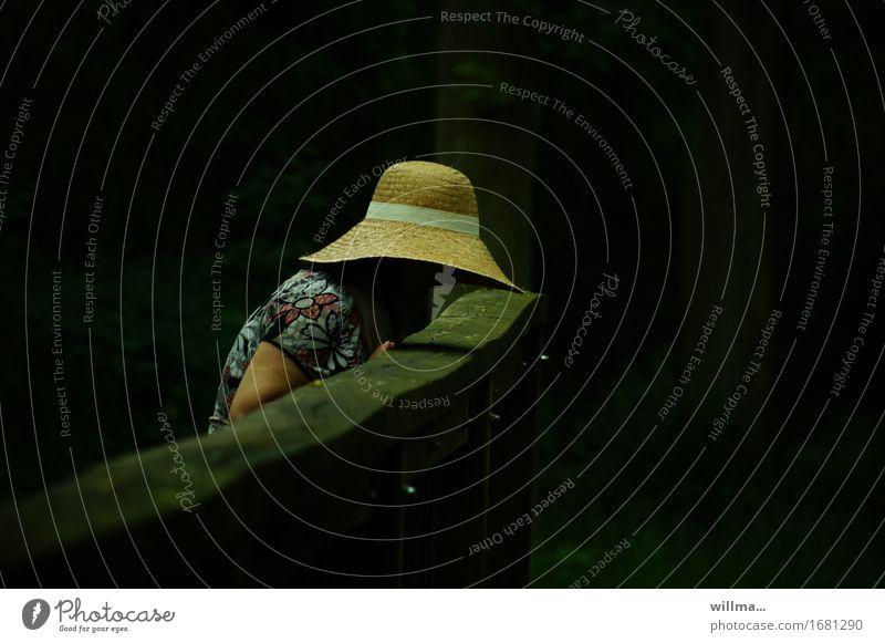 frau mir strohut beugt sich über das geländer einer holzbrücke vordunklem hintergrund feminin Frau Erwachsene Hut Strohhut dunkel Neugier schwarz Hoffnung