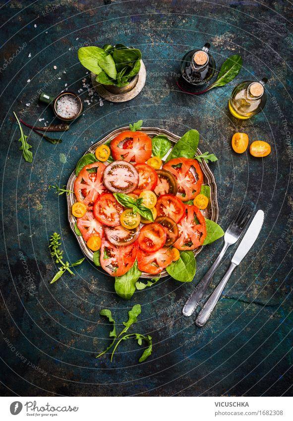 Tomatensalat mit bunten Tomaten , Besteck und Dressing Lebensmittel Gemüse Salat Salatbeilage Kräuter & Gewürze Öl Ernährung Festessen Bioprodukte