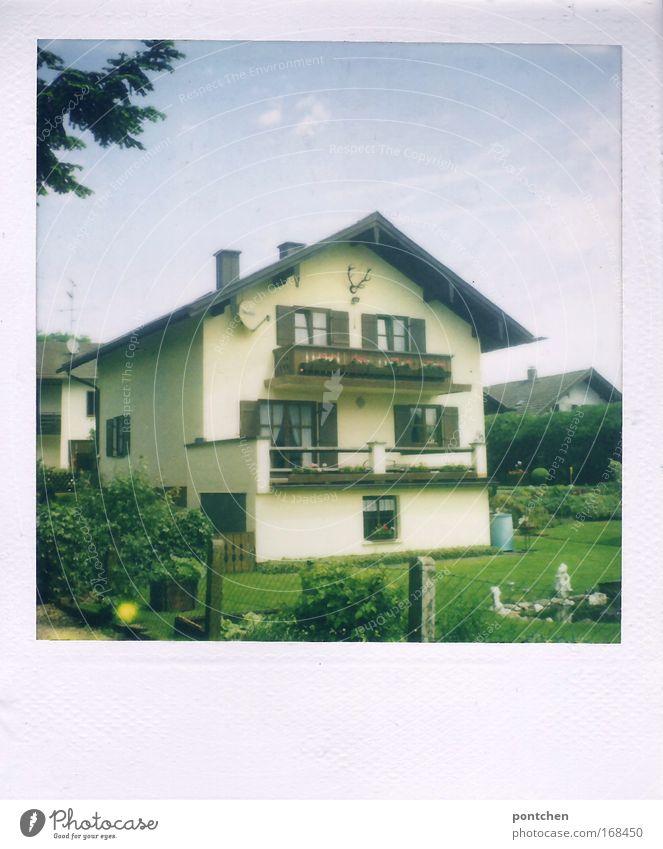Ein typisch bayerisches Einfamilienhaus mit Balkonen und einem Hirschgeweih. Häuser im Hintergrund und Garten im Vordergrund. Siedlung in einer ländlichen Gegend. Nachbarschaft