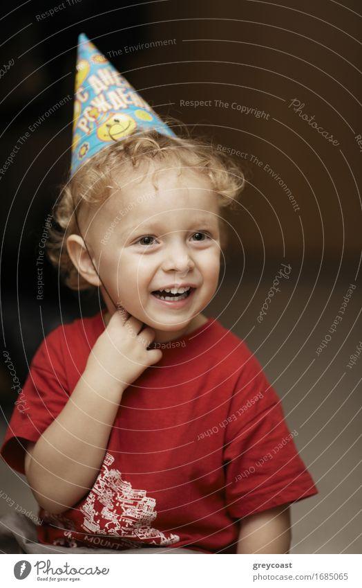 Nette glückliche junge Junge in einer Partei Hut lachen mit Freude, wie er einen Geburtstag oder Weihnachten feiert Lifestyle Glück schön Gesicht