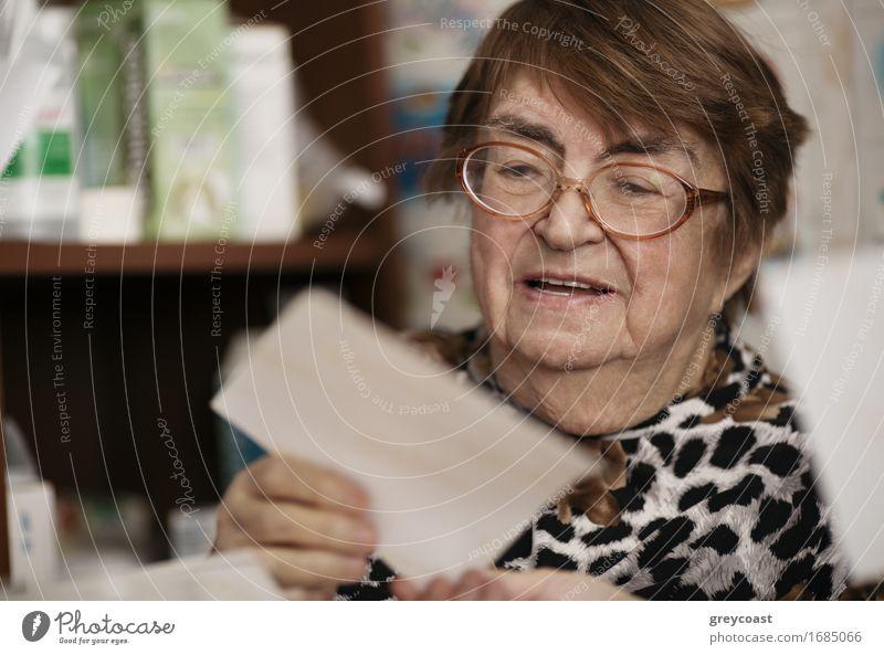 Ältere Frau mit Brille sitzt in ihrem Wohnzimmer und liest einen Brief, Nahaufnahme Porträt Lifestyle Gesicht lesen Lehrer Ruhestand Mensch Erwachsene