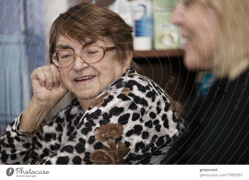 Ältere Dame, die zu einer jüngeren Frau plaudert Mensch alt weiß Gesicht Erwachsene Senior Lifestyle Glück sitzen Fröhlichkeit 60 und älter Lächeln
