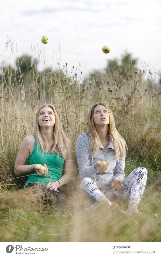 Zwei spielerische Mädchen, die draußen jonglieren Mensch Frau Himmel Natur Ferien & Urlaub & Reisen Jugendliche Sommer schön grün Junge Frau Hand Erholung