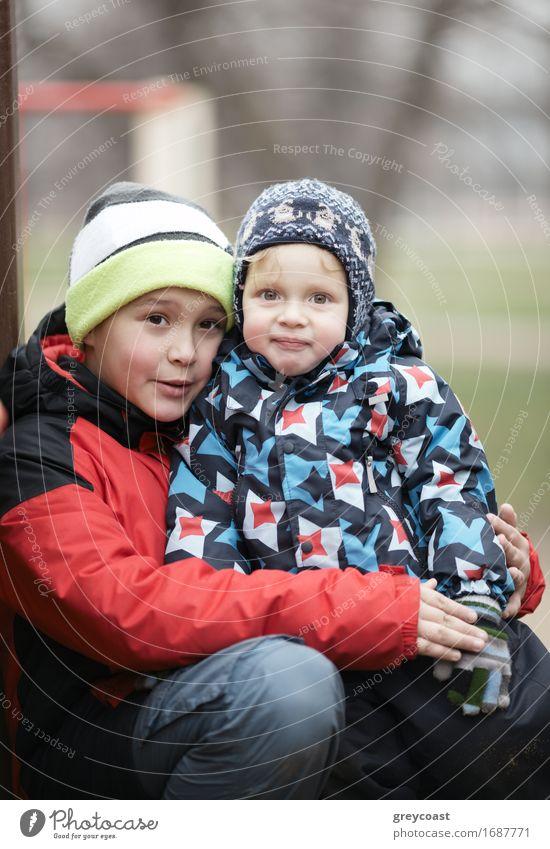Zwei entzückende junge Brüder im Freien im Winter warm eingepackt gegen das kalte Wetter mit dem älteren Jungen kuscheln sein Kleinkind Geschwister auf dem Schoß