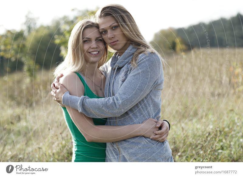 Zwei liebende Schwestern, die sich gegenseitig trösten und sich eng umarmen, während sie im Freien auf dem Lande stehen Lifestyle Glück schön Freizeit & Hobby