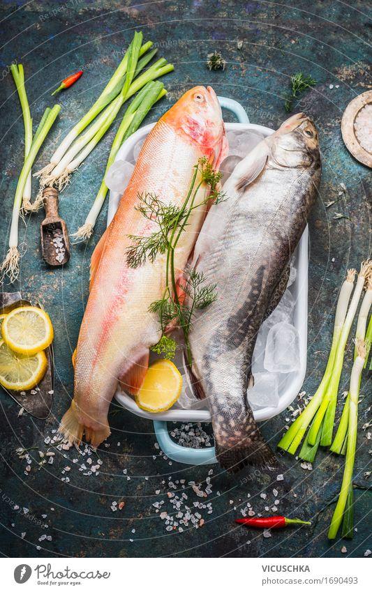 Forellen mit Eiswürfeln und frischen Zutaten fürs Kochen Lebensmittel Fisch Gemüse Kräuter & Gewürze Ernährung Mittagessen Abendessen Bioprodukte Diät Geschirr