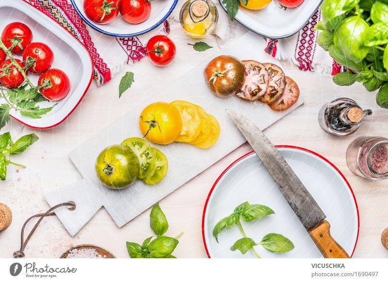 Scheiben von bunten Tomaten mit Messer Lebensmittel Gemüse Salat Salatbeilage Kräuter & Gewürze Öl Ernährung Mittagessen Abendessen Büffet Brunch Festessen