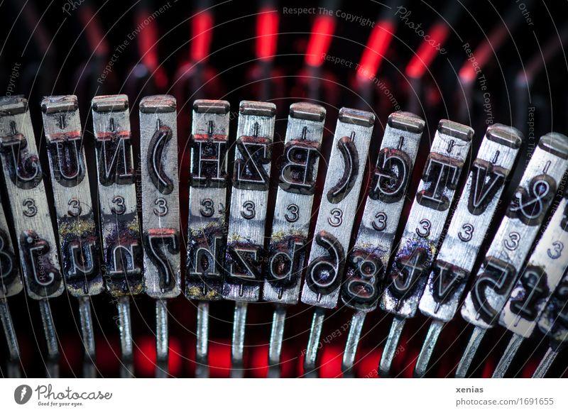 Typenhebel einer Schreibmaschine mit rotem Leuchten im Hintergrund Buchstaben Druckmaschine Schriftzeichen Ziffern & Zahlen schreiben schwarz silber leuchten