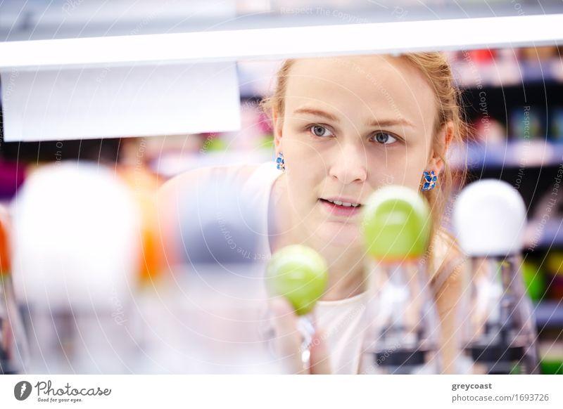 Junge blonde Frau, die sorgfältig Produkte in einem Geschäft analysiert - Blick durch Produkte kaufen Junge Frau Jugendliche Erwachsene 1 Mensch 18-30 Jahre