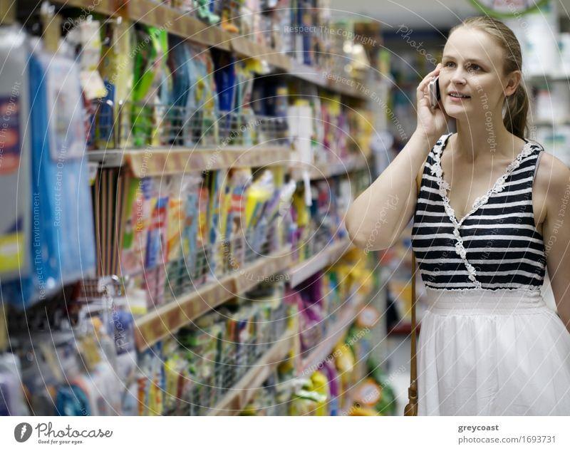 Frau mit langem blonden Pferdeschwanz, die beim Einkaufen in einem Gang im Supermarkt mit ihrem Handy telefoniert Glück Telefon Funktelefon PDA Mensch