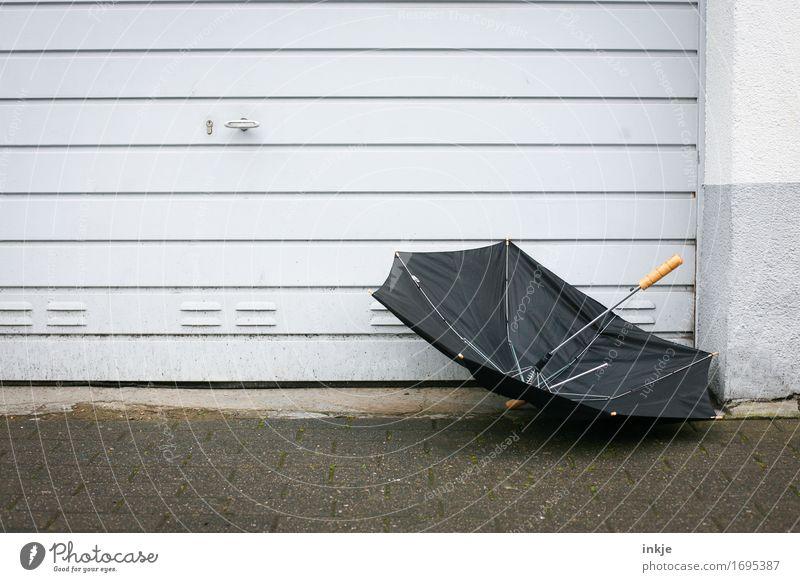 schwarzsehen | deutscher Sommer Wetter schlechtes Wetter Wind Sturm Regen Menschenleer Mauer Wand Fassade Garagentor Regenschirm trist grau kaputt fliegen