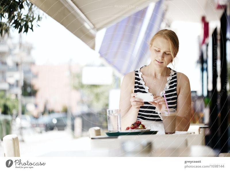 Attraktive Frau, die ein Gebäck mit ihrem Smartphone fotografiert, während sie an einem Tisch in einem Open-Air-Restaurant sitzt und Erfrischungen genießt