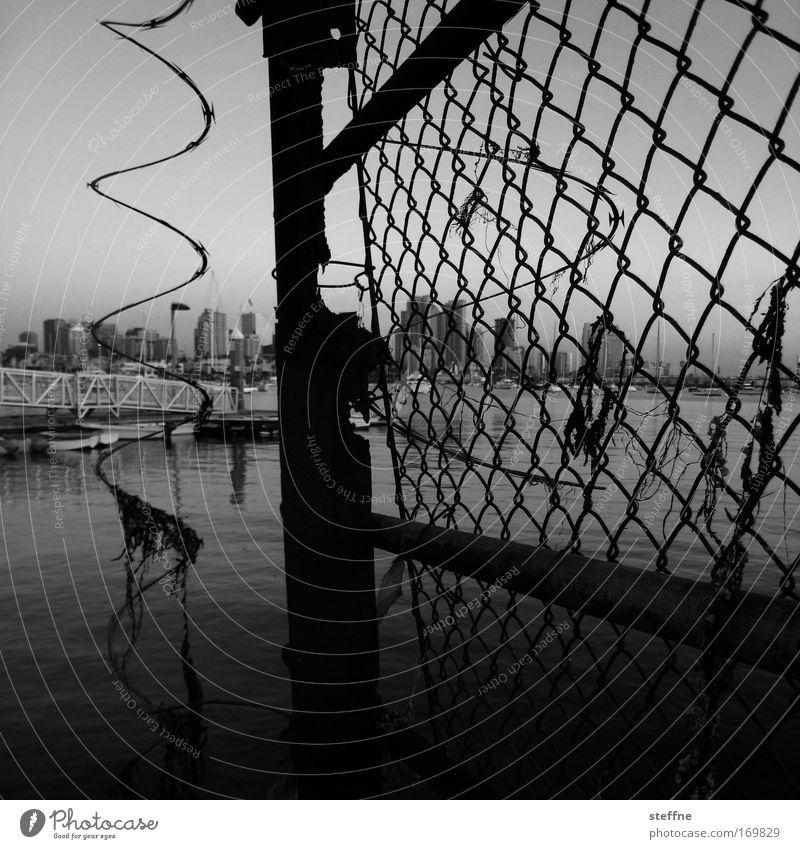 Moschendrohtßaun Schwarzweißfoto Außenaufnahme Dämmerung San Diego USA Hafenstadt Skyline Zaun Maschendrahtzaun dunkel kaputt Stadt
