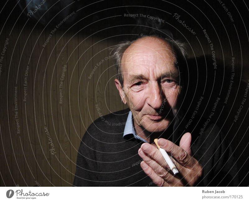 Großvater raucht. Farbfoto Innenaufnahme Textfreiraum links Hintergrund neutral Schatten Kontrast Porträt Blick in die Kamera Blick nach vorn Rauchen maskulin
