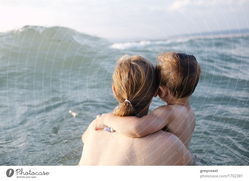 Mutter schwimmt im Meer mit ihrem kleinen Sohn im Arm und beobachtet eine entgegenkommende Welle, Blick von hinten Erholung Ferien & Urlaub & Reisen Sommer Kind