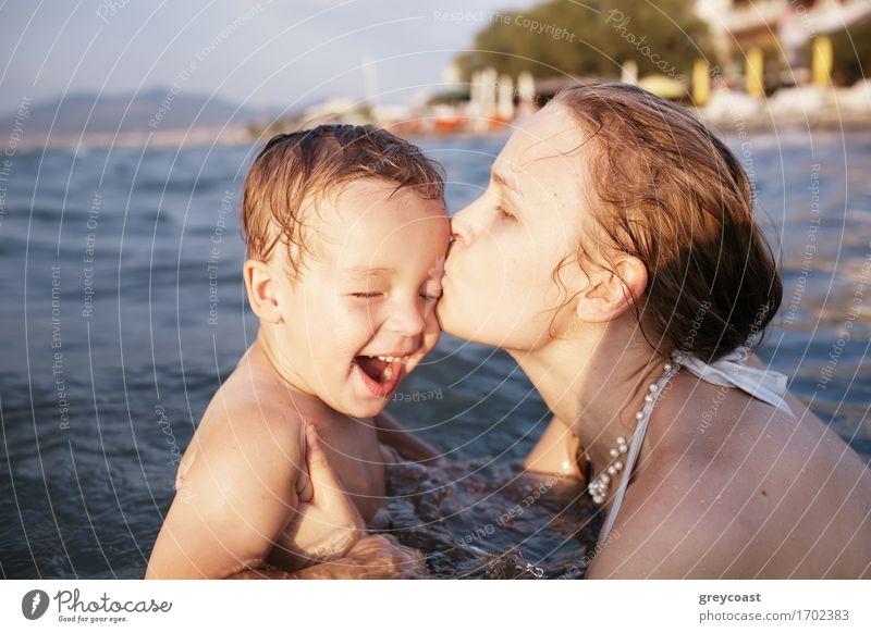 Mutter küsst ihr kleines Kind beim Baden im Meerwasser während des Sonnenuntergangs Spielen Ferien & Urlaub & Reisen Strand Wellen Mensch Junge Junge Frau