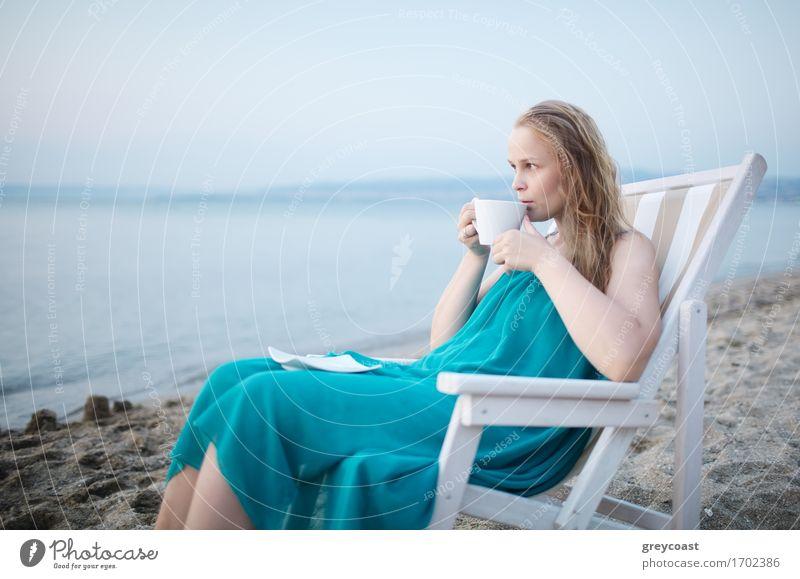 Weite Aufnahme eines jungen Mädchens, das eine Tasse Tee am Meer genießt, auf einem Liegestuhl sitzend und mit einem glückseligen Gesichtsausdruck mit Blick auf einen tropischen Strand