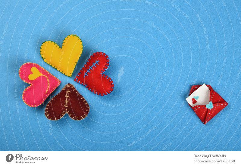 Vier bunte handgemachte genähte Spielzeugherzen auf blauem Filz Lifestyle Design Freizeit & Hobby Basteln Handarbeit Valentinstag Kunst Kunstwerk Herz Liebe