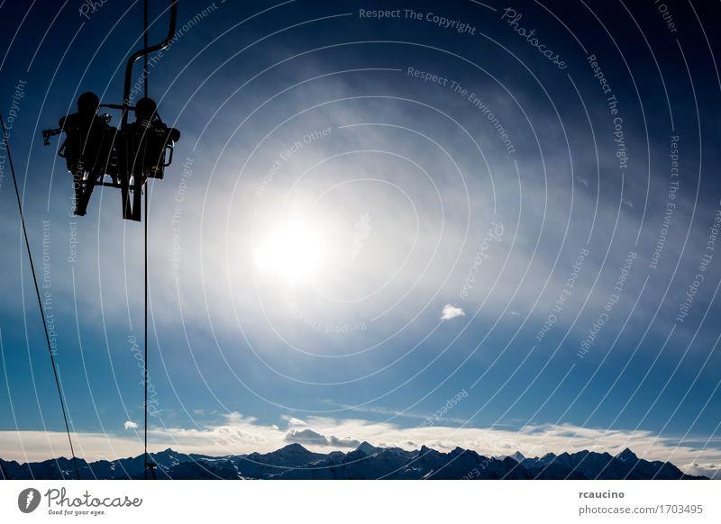 Zwei Skifahrer in einem Sessellift von der Sonne hinterleuchtet Ferien & Urlaub & Reisen Tourismus Winter Schnee Berge u. Gebirge Stuhl Sport Skifahren Mensch