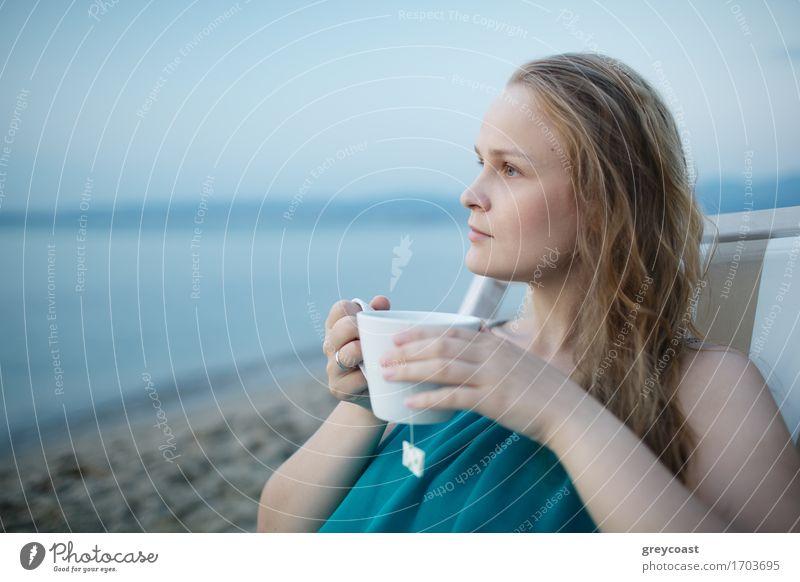 Frau, die eine Tasse Tee am Meer genießt, sitzt entspannt auf einem Liegestuhl mit einem glückseligen Ausdruck mit Blick auf einen tropischen Strand Getränk