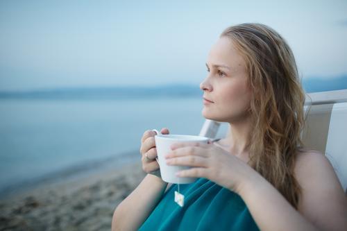 Frau, die eine Tasse Tee an der Küste genießt Mensch Ferien & Urlaub & Reisen Jugendliche blau Sommer schön Junge Frau Meer Erholung ruhig Mädchen Strand
