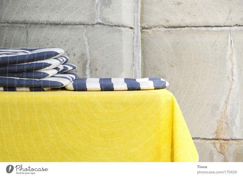 blau-weiße Sitzkissen auf gelbem Tischtuch vor Betonwand Farbfoto mehrfarbig Außenaufnahme Nahaufnahme Textfreiraum unten Tag Café Kissen gestreift Sommer