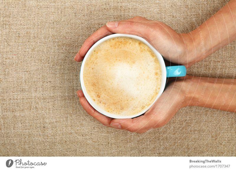 Zwei Frauenhände halten Lattecappuccino-Kaffeetasse auf Segeltuch Jugendliche Junge Frau Hand Erholung Erwachsene braun Aussicht genießen Warmherzigkeit Getränk