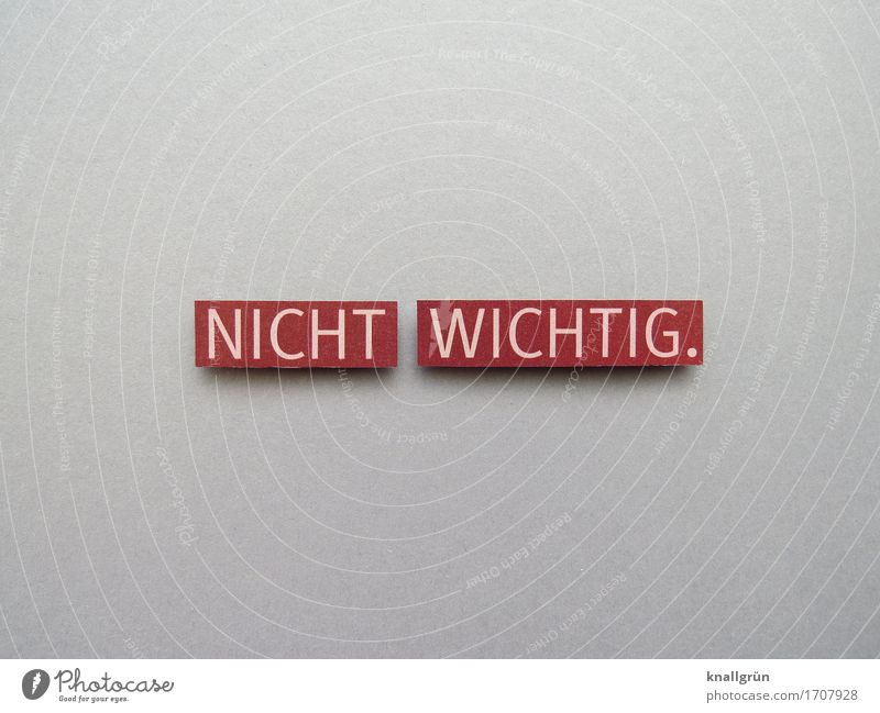 NICHT WICHTIG. Schriftzeichen Schilder & Markierungen Kommunizieren eckig grau rot weiß Gefühle Gelassenheit Gleichgültigkeit Farbfoto Studioaufnahme