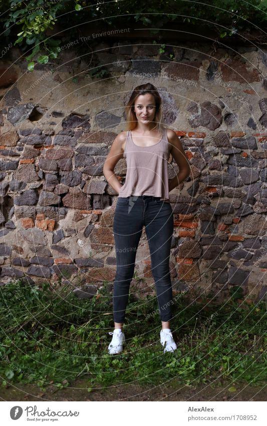 angelockt Freude schön sportlich Junge Frau Jugendliche 18-30 Jahre Erwachsene Landschaft Efeu Mauer Wand Jeanshose Top Turnschuh blond langhaarig Kommunizieren