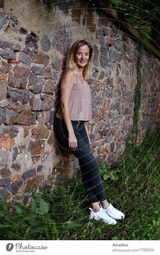angelehnt elegant schön Ausflug Junge Frau Jugendliche 18-30 Jahre Erwachsene Landschaft Schönes Wetter Gras Efeu Park Mauer Wand T-Shirt Jeanshose Turnschuh
