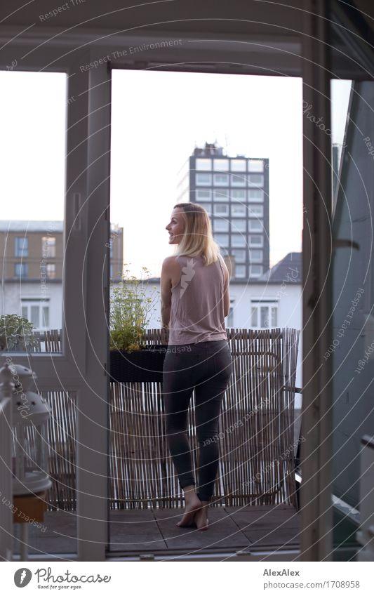 Wachstum in Balkonien I Häusliches Leben Balkonpflanze Balkontür Junge Frau Jugendliche 18-30 Jahre Erwachsene Landschaft Schönes Wetter Stadt Hochhaus T-Shirt