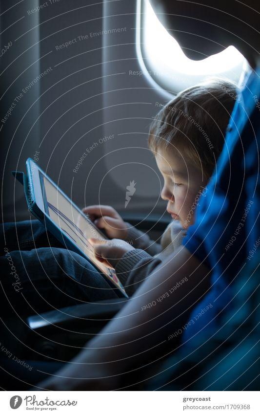 Kleiner Junge sitzt während eines Fluges in seinem Sitz und spielt zufrieden mit einem Tablet-Computer in einem Flugzeug, beobachtet von seiner Mutter