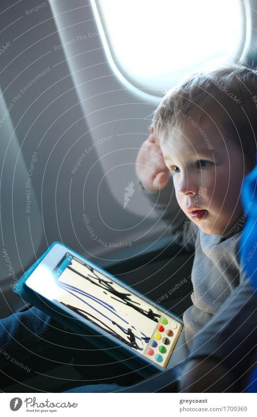 Zeichnung des kleinen Jungen auf einer Tablette in einem Flugzeug Mensch Kind Ferien & Urlaub & Reisen Spielen Kunst fliegen Freizeit & Hobby modern blond