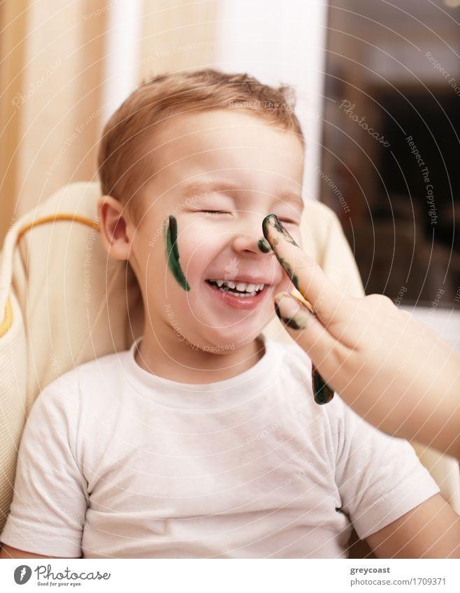 Kleiner Junge lacht, als seine Mutter malt sein Gesicht Streifung seine Wange und tupft seine Nase mit schwarzer Farbe Gesicht Freude Glück Freizeit & Hobby