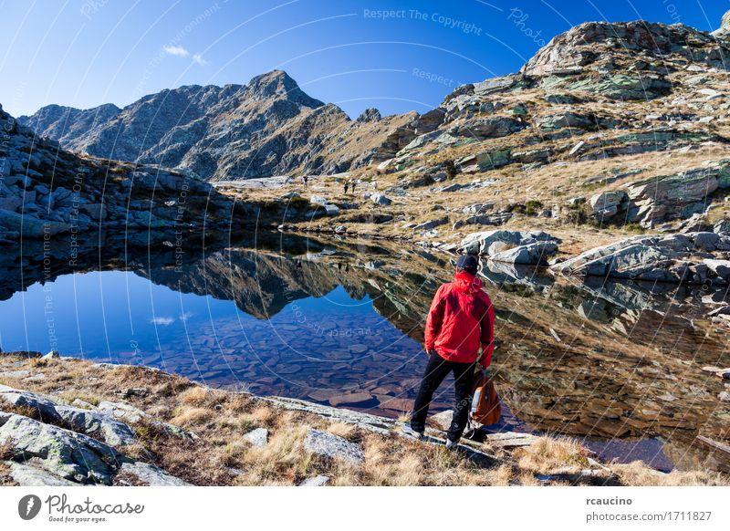 Männlicher Wanderer nahe einem kleinen Gebirgssee. Mensch Himmel Natur Ferien & Urlaub & Reisen Mann Sommer Landschaft rot Einsamkeit Berge u. Gebirge