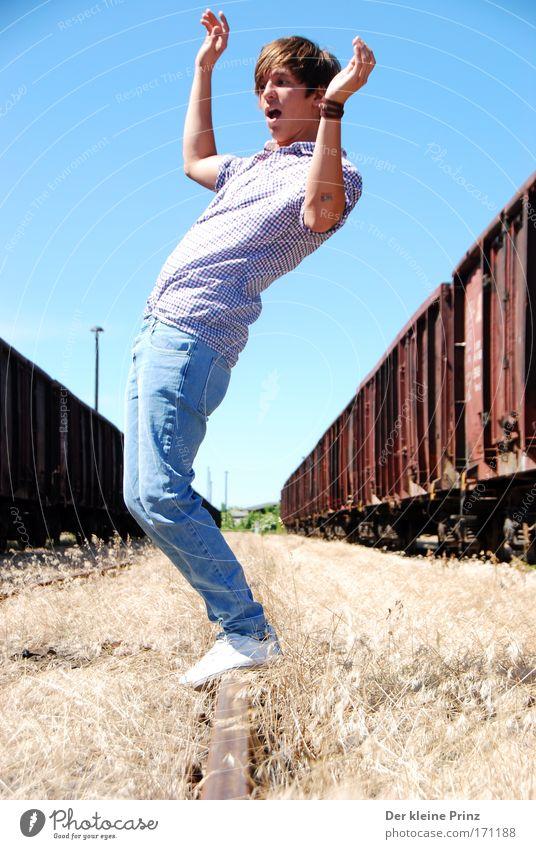 Der erstaunte junge Mann vor alten Güterwagons Mensch Jugendliche schön Freude Zufriedenheit modern frisch wild Fröhlichkeit Eisenbahn Hoffnung Coolness