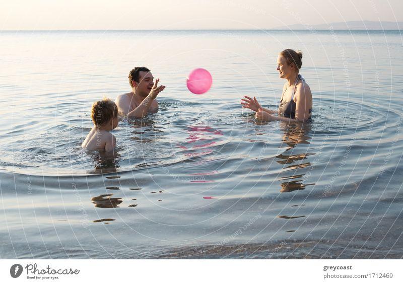 Junge Familie, die mit Ball bei Sonnenuntergang spielt Freude Glück Freizeit & Hobby Spielen Ferien & Urlaub & Reisen Sommer Strand Meer Kind Baby Mutter