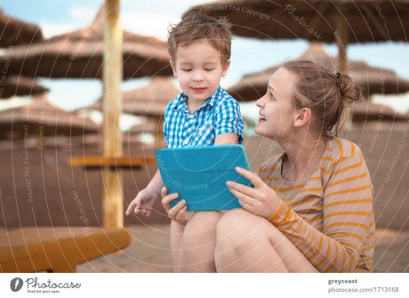 Kleiner Junge mit seiner Mutter in einem Strandresort spielen mit einem Tablet-Computer am Strand unter Stroh Sonnenschirme Freude Glück Spielen