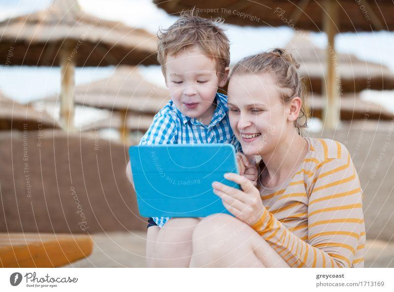 Glückliche Mutter und ihr kleiner Sohn in einem Strandresort spielen auf einem Tablet-Computer zusammen unter Sonnenschirmen am Meer Freude Spielen