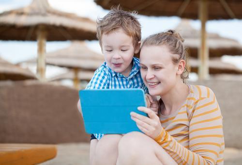 Glückliche Mutter und Sohn in einem Strandurlaubsort Freude Spielen Entertainment Kindererziehung Schule PDA Computer Technik & Technologie Internet Mensch