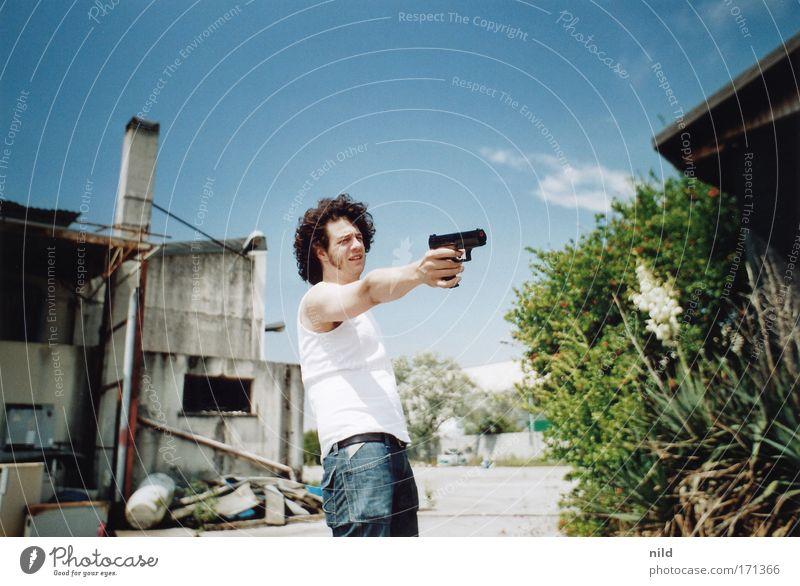 Actionfilm – Steve Shooting Farbfoto Außenaufnahme Textfreiraum oben Tag Kontrast Sonnenlicht Zentralperspektive Oberkörper Blick nach vorn Mensch maskulin