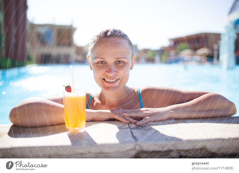 Lächelnde junge Frau, die ein erfrischendes Orangengetränk oder einen Cocktail im Pool genießt und ihre Arme auf die Poolumrandung stützt und in die Kamera lächelt