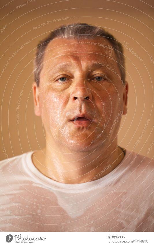 Müde aussehende heiß schwitzende Mann mittleren Alters nach einem Training, Nahaufnahme Kopf und Schultern Porträt Blick direkt in die Kamera Gesicht