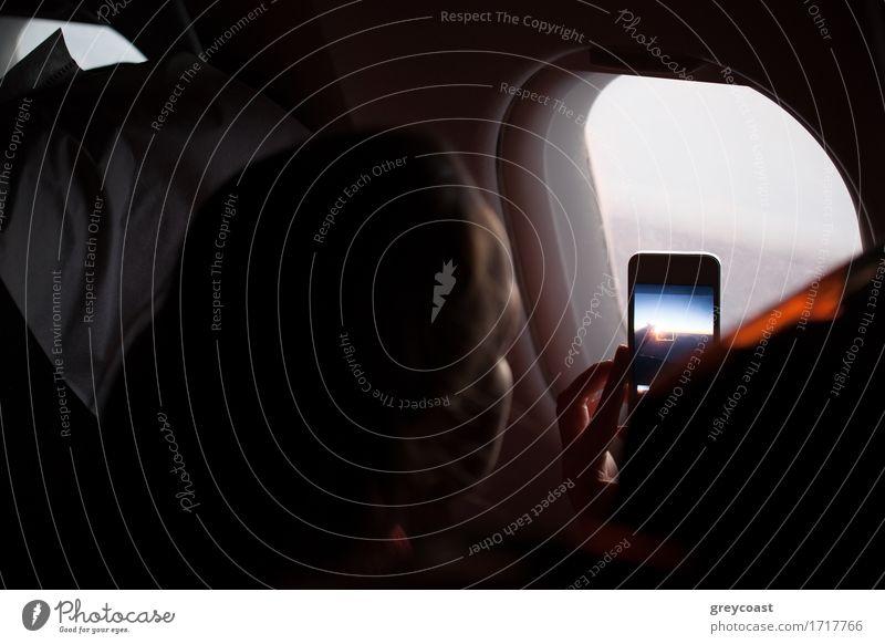 Frau, die Fotos durch ein Kabinenöffnungsloch macht Mensch Jugendliche Junge Frau 18-30 Jahre Erwachsene oben Verkehr Ausflug Aussicht Fotografie Flugzeug