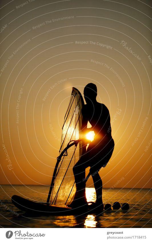 Mann sailboarding bei Sonnenuntergang Silhouette gegen die helle Kugel der Sonne in einem bunten orange Himmel auf einem ruhigen Meer Erholung